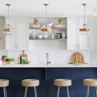Inspiration for a transitional galley ceramic tile open concept kitchen remodel in Minneapolis with shaker cabinets, white cabinets, quartz countertops, white backsplash, stainless steel appliances, white countertops, an undermount sink, subway tile backsplash and an island