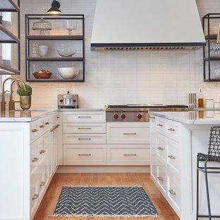 Foto på ett stort vintage vit kök, med en undermonterad diskho, släta luckor, vita skåp, bänkskiva i kvartsit, vitt stänkskydd, stänkskydd i tunnelbanekakel, rostfria vitvaror, ljust trägolv, en köksö och gult golv