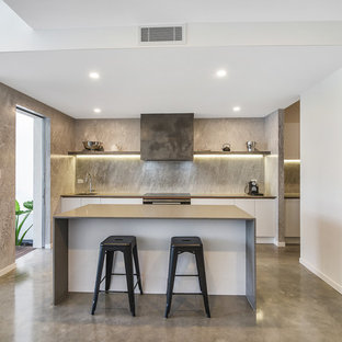 Photo of a contemporary single-wall kitchen in Sunshine Coast with an undermount sink, flat-panel cabinets, white cabinets, grey splashback, black appliances, concrete floors, with island, grey floor and grey benchtop.