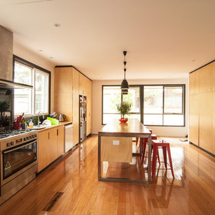 Photo of a large contemporary galley kitchen in Melbourne with a drop-in sink, flat-panel cabinets, medium wood cabinets, wood benchtops, black splashback, stainless steel appliances, medium hardwood floors and with island.