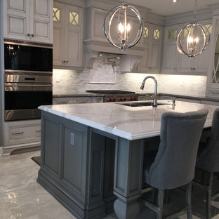Design ideas for a large transitional l-shaped eat-in kitchen in Toronto with an undermount sink, quartz benchtops, white splashback, mosaic tile splashback, white appliances, with island, white benchtop, recessed-panel cabinets, porcelain floors, stainless steel cabinets and grey floor.