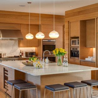 ボストンのビーチスタイルのおしゃれなアイランドキッチン (フラットパネル扉のキャビネット、淡色木目調キャビネット、白いキッチンパネル、石スラブのキッチンパネル、パネルと同色の調理設備、淡色無垢フローリング、白いキッチンカウンター) の写真