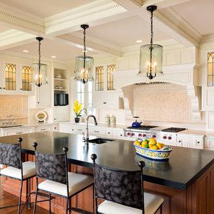 Foto di una grande cucina chic con lavello sottopiano, ante con bugna sagomata, ante bianche, elettrodomestici in acciaio inossidabile, parquet scuro, isola, top in saponaria, paraspruzzi bianco e paraspruzzi con piastrelle in ceramica