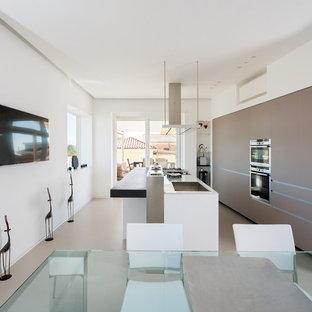 Ejemplo de cocina comedor lineal, actual, extra grande, con armarios tipo vitrina, puertas de armario beige, electrodomésticos de acero inoxidable, suelo de baldosas de porcelana y una isla
