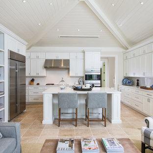 Aménagement d'une cuisine bord de mer en U avec un placard avec porte à panneau encastré, des portes de placard blanches, une crédence blanche, un électroménager en acier inoxydable, un îlot central et un sol beige.