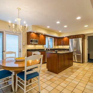 Design ideas for a mid-sized traditional u-shaped separate kitchen in Other with an undermount sink, raised-panel cabinets, medium wood cabinets, granite benchtops, stainless steel appliances, ceramic floors, with island, yellow floor and black benchtop.