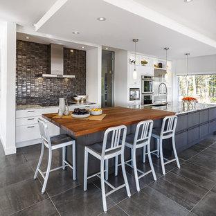 Zweizeilige, Große Moderne Wohnküche mit weißen Schränken, Arbeitsplatte aus Holz, Küchenrückwand in Metallic, Kücheninsel, Rückwand aus Metallfliesen, Unterbauwaschbecken, Küchengeräten aus Edelstahl, Porzellan-Bodenfliesen, flächenbündigen Schrankfronten und grauem Boden in Ottawa