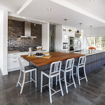 Eat-in kitchen - large contemporary galley porcelain tile and gray floor eat-in kitchen idea in Ottawa with white cabinets, wood countertops, metallic backsplash, an island, metal backsplash, an undermount sink, stainless steel appliances and flat-panel cabinets