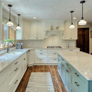 他の地域のトランジショナルスタイルのおしゃれなアイランドキッチン (アンダーカウンターシンク、白いキャビネット、クオーツストーンカウンター、白いキッチンパネル、サブウェイタイルのキッチンパネル、シルバーの調理設備の、クッションフロア、茶色い床、ベージュのキッチンカウンター) の写真