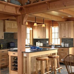 Modelo de cocina rural con puertas de armario de madera clara, suelo de pizarra y salpicadero de pizarra