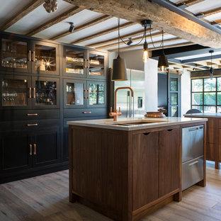 Aménagement d'une cuisine américaine montagne avec un évier encastré, un placard à porte plane, des portes de placard en bois brun, un électroménager en acier inoxydable, un sol en bois clair, un îlot central, un sol beige et un plan de travail beige.