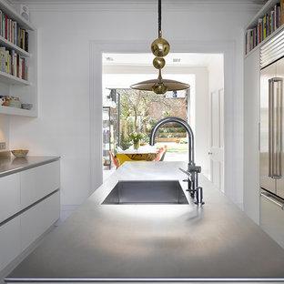 Bild på ett mellanstort funkis grå grått kök, med släta luckor, vita skåp, bänkskiva i rostfritt stål, grått stänkskydd, rostfria vitvaror, målat trägolv, en köksö och vitt golv