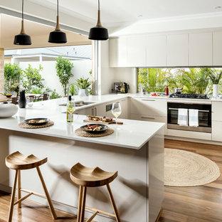Offene Moderne Küche in U-Form mit Doppelwaschbecken, flächenbündigen Schrankfronten, beigen Schränken, Rückwand-Fenster, Küchengeräten aus Edelstahl, braunem Holzboden, Halbinsel und braunem Boden in Perth