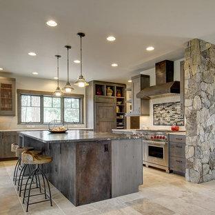 デンバーの広いラスティックスタイルのおしゃれなキッチン (落し込みパネル扉のキャビネット、濃色木目調キャビネット、シルバーの調理設備、御影石カウンター、マルチカラーのキッチンパネル、ボーダータイルのキッチンパネル、トラバーチンの床、ベージュの床) の写真