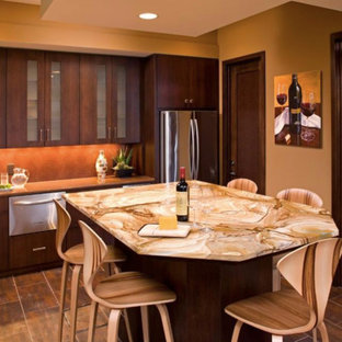 Design ideas for a large u-shaped eat-in kitchen in Minneapolis with an undermount sink, flat-panel cabinets, dark wood cabinets, onyx benchtops, red splashback, mosaic tile splashback, stainless steel appliances, porcelain floors, with island, brown floor and orange benchtop.