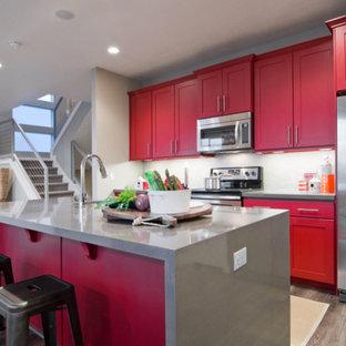 Offene, Zweizeilige, Mittelgroße Klassische Küche mit Küchenrückwand in Weiß, Küchengeräten aus Edelstahl, Waschbecken, Schrankfronten im Shaker-Stil, roten Schränken, Vinylboden, Kücheninsel und Mineralwerkstoff-Arbeitsplatte in Salt Lake City