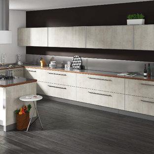 タンパの大きいモダンスタイルのおしゃれなキッチン (ドロップインシンク、フラットパネル扉のキャビネット、グレーのキャビネット、人工大理石カウンター、グレーのキッチンパネル、シルバーの調理設備の、磁器タイルの床、グレーの床、白いキッチンカウンター) の写真
