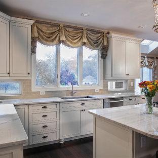 他の地域の大きい地中海スタイルのおしゃれなキッチン (シングルシンク、フラットパネル扉のキャビネット、赤いキャビネット、珪岩カウンター、ベージュキッチンパネル、ガラスタイルのキッチンパネル、シルバーの調理設備の、無垢フローリング、茶色い床) の写真