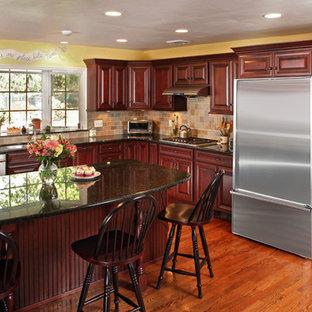 他の地域の大きいトランジショナルスタイルのおしゃれなキッチン (シングルシンク、レイズドパネル扉のキャビネット、赤いキャビネット、タイルカウンター、ベージュキッチンパネル、セラミックタイルのキッチンパネル、シルバーの調理設備の、無垢フローリング、赤い床) の写真