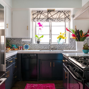 This is an example of a small eclectic u-shaped separate kitchen in Los Angeles with a double-bowl sink, flat-panel cabinets, white cabinets, tile benchtops, multi-coloured splashback, mosaic tile splashback, stainless steel appliances, vinyl floors, no island, brown floor and white benchtop.