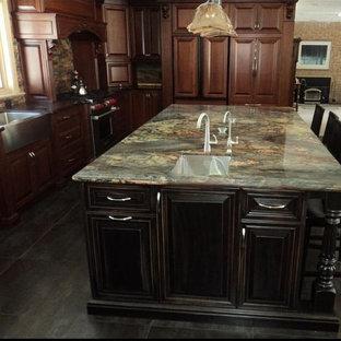 トロントの大きいトラディショナルスタイルのおしゃれなキッチン (エプロンフロントシンク、レイズドパネル扉のキャビネット、濃色木目調キャビネット、御影石カウンター、マルチカラーのキッチンパネル、ボーダータイルのキッチンパネル、パネルと同色の調理設備、スレートの床、黒い床、緑のキッチンカウンター) の写真