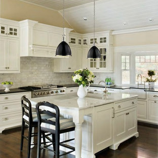 Large contemporary eat-in kitchen designs - Example of a large trendy l-shaped dark wood floor eat-in kitchen design in Providence with a farmhouse sink, recessed-panel cabinets, white cabinets, marble countertops, white backsplash, ceramic backsplash, stainless steel appliances and an island