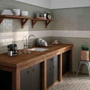 ポートランド(メイン)の中くらいのカントリー風おしゃれなキッチン (アンダーカウンターシンク、フラットパネル扉のキャビネット、濃色木目調キャビネット、木材カウンター、グレーのキッチンパネル、サブウェイタイルのキッチンパネル、セメントタイルの床、アイランドなし、マルチカラーの床) の写真