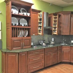 Свежая идея для дизайна: п-образная кухня среднего размера в современном стиле с обеденным столом, врезной раковиной, фасадами с выступающей филенкой, темными деревянными фасадами, столешницей из гранита, серым фартуком, фартуком из плитки кабанчик, техникой из нержавеющей стали, полом из бамбука, островом и коричневым полом - отличное фото интерьера