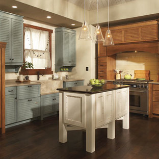 Design ideas for a small country l-shaped eat-in kitchen in Sacramento with louvered cabinets, medium wood cabinets, solid surface benchtops, beige splashback, timber splashback, stainless steel appliances, dark hardwood floors and with island.