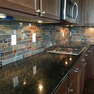 Rustikale Küche mit Schrankfronten mit vertiefter Füllung, dunklen Holzschränken, Granit-Arbeitsplatte, bunter Rückwand, Rückwand aus Schiefer, Küchengeräten aus Edelstahl, dunklem Holzboden und braunem Boden in Denver