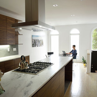 Inspiration for a large eclectic galley separate kitchen in Orange County with an undermount sink, flat-panel cabinets, dark wood cabinets, marble benchtops, grey splashback, stone tile splashback, stainless steel appliances, limestone floors and a peninsula.