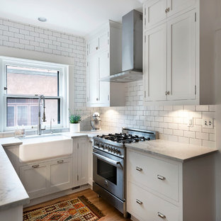 Traditional enclosed kitchen ideas - Enclosed kitchen - traditional l-shaped light wood floor enclosed kitchen idea in Denver with a farmhouse sink, shaker cabinets, white cabinets, marble countertops, white backsplash, subway tile backsplash and stainless steel appliances
