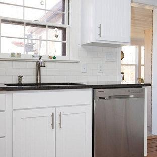 Esempio di una cucina design di medie dimensioni con lavello a doppia vasca, ante bianche, top in granito, paraspruzzi bianco, elettrodomestici in acciaio inossidabile, isola, ante a persiana, paraspruzzi con piastrelle diamantate, pavimento in legno massello medio, pavimento marrone e top nero