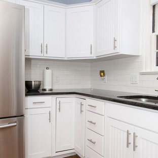 Design ideas for a mid-sized contemporary l-shaped eat-in kitchen in Other with a double-bowl sink, white cabinets, granite benchtops, white splashback, stainless steel appliances, with island, louvered cabinets, subway tile splashback, medium hardwood floors, brown floor and black benchtop.