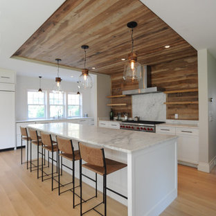 Mid-sized beach style l-shaped open plan kitchen in Boston with an undermount sink, shaker cabinets, white cabinets, marble benchtops, timber splashback, stainless steel appliances, light hardwood floors, with island and beige floor.