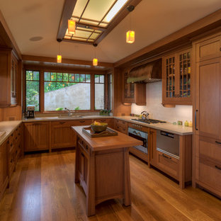 Craftsman kitchen ideas - Inspiration for a craftsman u-shaped medium tone wood floor and orange floor kitchen remodel in San Francisco with a drop-in sink, glass-front cabinets, medium tone wood cabinets, wood countertops, white backsplash, paneled appliances and an island