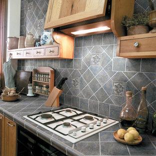Foto de cocina clásica, de tamaño medio, con armarios con paneles lisos, puertas de armario marrones, encimera de azulejos, salpicadero verde, salpicadero de piedra caliza y electrodomésticos negros