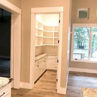 На фото: п-образная кухня среднего размера в стиле кантри с кладовкой, фасадами с выступающей филенкой, белыми фасадами, столешницей из гранита, паркетным полом среднего тона, островом и бежевым полом с