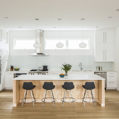 Example of a mid-sized danish l-shaped light wood floor eat-in kitchen design in Little Rock with an undermount sink, flat-panel cabinets, white cabinets, quartz countertops, white backsplash, glass tile backsplash, stainless steel appliances and an island