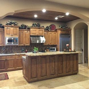 フェニックスの中サイズの地中海スタイルのおしゃれなキッチン (アンダーカウンターシンク、レイズドパネル扉のキャビネット、中間色木目調キャビネット、御影石カウンター、マルチカラーのキッチンパネル、ボーダータイルのキッチンパネル、シルバーの調理設備の、トラバーチンの床、ベージュの床) の写真