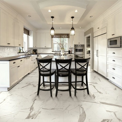 Inspiration for a large transitional u-shaped marble floor eat-in kitchen remodel in New York with a farmhouse sink, shaker cabinets, white cabinets, soapstone countertops, white backsplash, porcelain backsplash, stainless steel appliances and an island