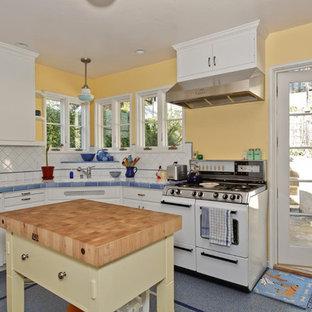 Ejemplo de cocina en L, ecléctica, de tamaño medio, con despensa, armarios estilo shaker, puertas de armario azules, encimera de azulejos, salpicadero blanco, salpicadero de azulejos de cerámica, electrodomésticos blancos, suelo de terrazo, una isla y suelo azul