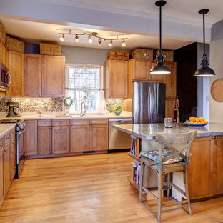 Photo of a large arts and crafts l-shaped eat-in kitchen in Orange County with an undermount sink, shaker cabinets, medium wood cabinets, zinc benchtops, beige splashback, stone tile splashback, stainless steel appliances, light hardwood floors and with island.