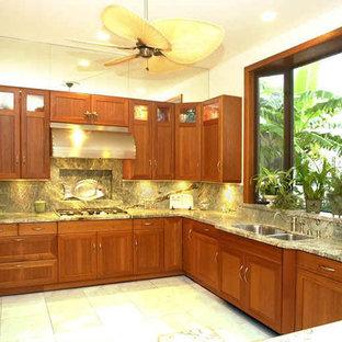 ハワイの大きいトロピカルスタイルのおしゃれなコの字型キッチン (ダブルシンク、シェーカースタイル扉のキャビネット、中間色木目調キャビネット、大理石カウンター、緑のキッチンパネル、大理石のキッチンパネル、パネルと同色の調理設備、アイランドなし) の写真
