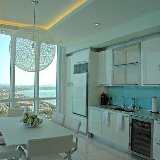 Immagine di una piccola cucina minimal con lavello a doppia vasca, ante lisce, ante bianche, top alla veneziana, paraspruzzi blu, paraspruzzi con lastra di vetro, elettrodomestici da incasso, pavimento in marmo, nessuna isola e pavimento beige