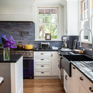 Photo of a traditional l-shaped kitchen in Los Angeles with a farmhouse sink, shaker cabinets, white cabinets, blue splashback, coloured appliances and slate splashback.