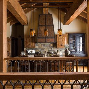 サクラメントの大きいラスティックスタイルのおしゃれなキッチン (レイズドパネル扉のキャビネット、中間色木目調キャビネット、木材カウンター、マルチカラーのキッチンパネル、スレートのキッチンパネル、パネルと同色の調理設備、無垢フローリング、茶色い床) の写真
