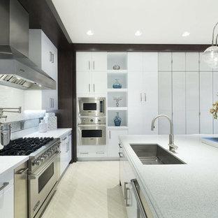 マイアミの中サイズのコンテンポラリースタイルのおしゃれなキッチン (アンダーカウンターシンク、フラットパネル扉のキャビネット、白いキャビネット、テラゾカウンター、シルバーの調理設備の) の写真