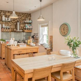 Ispirazione per una cucina abitabile country di medie dimensioni con top in legno, pavimento in terracotta, isola, pavimento arancione, nessun'anta e paraspruzzi con lastra di vetro