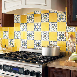 Mid-sized mediterranean kitchen pictures - Inspiration for a mid-sized mediterranean kitchen remodel in New York with ceramic backsplash, stainless steel appliances, an island, glass-front cabinets, medium tone wood cabinets and yellow backsplash